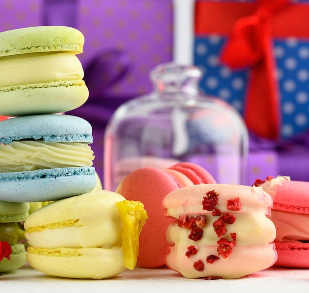 Baked macarons with different flavors and rosebuds on a white background, behind gift boxes, close up