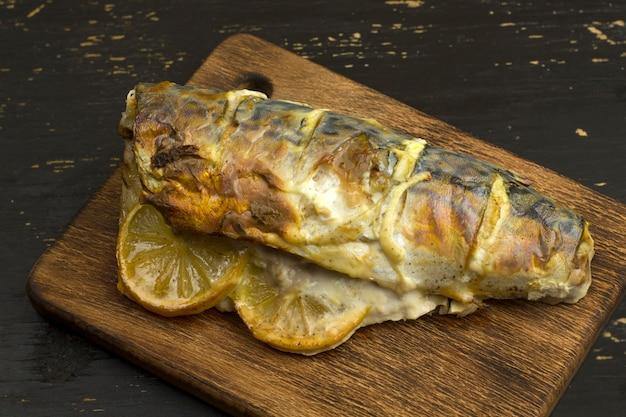 木の板にレモンと野菜を添えて焼きサバの死骸