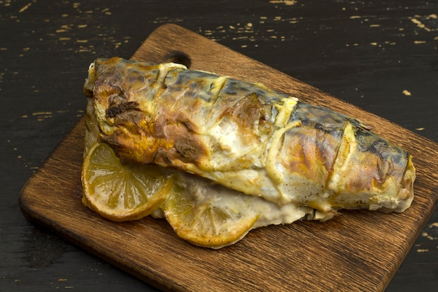 Baked mackerel carcass with lemon and vegetables on wooden board