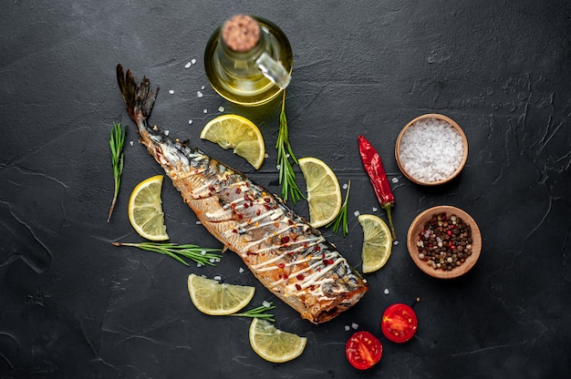 Baked mackerel on a cutting board with lemon and spices on a stone background, ready to eat