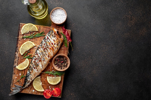 Baked mackerel on a cutting board with lemon and spices on a stone background