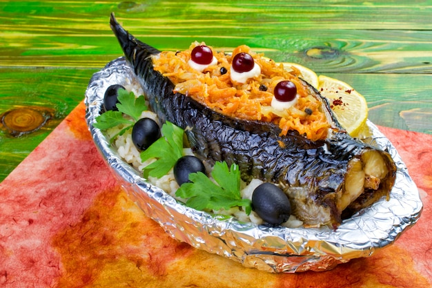 Baked mackerel fish stuffed with carrots, olives, parsley lies on a plate wrapped in foil.