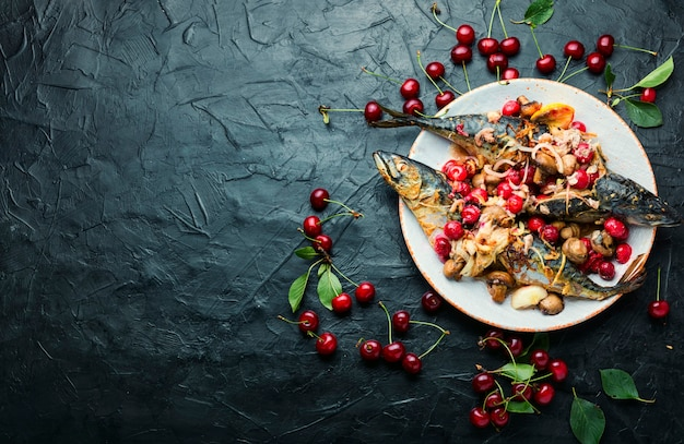 Baked mackerel with cherry sauce.fish filled with berries.scomber on the plate.copy space