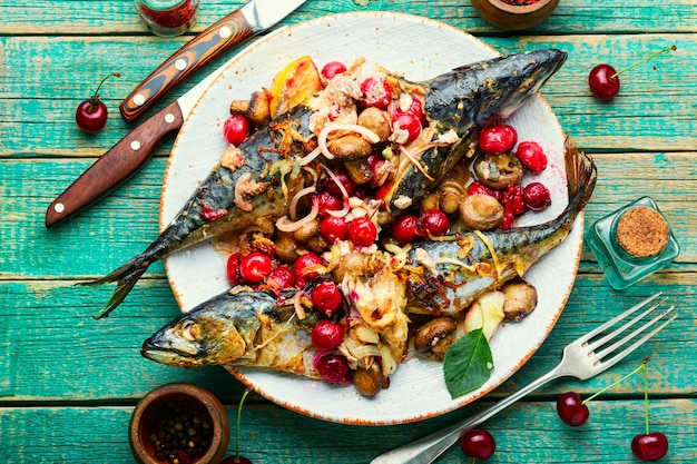 Baked mackerel with cherry sauce.fish filled with berries.scomber on the plate