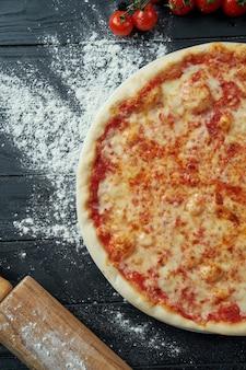 食材と組成の黒い木の表面にトマトと溶けたチーズ、赤いソースのマルガリータピザを焼き。上面図