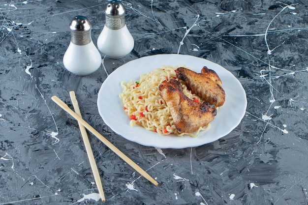Запеченное мясо и лапша на тарелке рядом с солью и палочками для еды на мраморной поверхности.