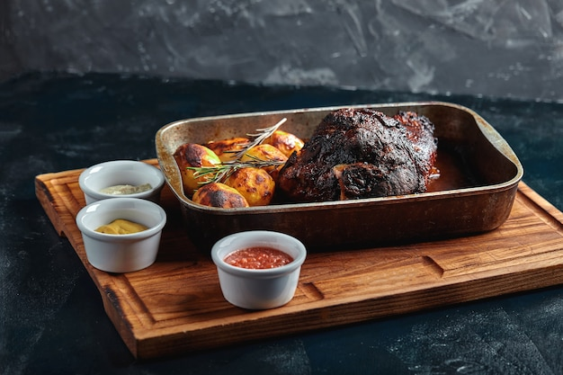 Baked meat and potatoes. delicious and hearty meal. large baked piece of meat. cooked hot food.