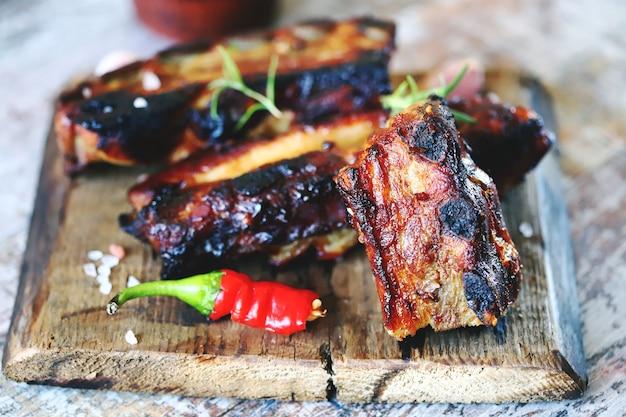 Запеченные мясные ребрышки. аппетитные острые ребрышки, запеченные в медово-горчичном соусе с перцем чили. ребрышки барбекю.