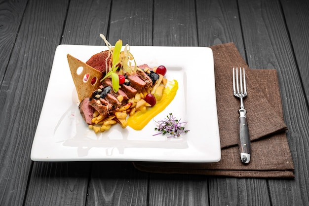 Запеченное мясо с жареным картофелем и ягодным соусом. блюдо в ресторане