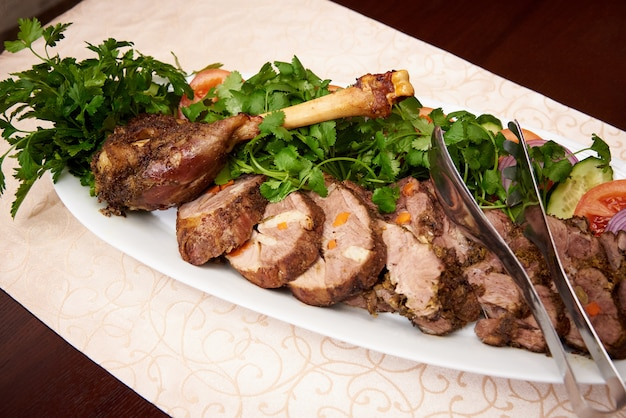 Baked meat with vegetables and parsley on a white plate.