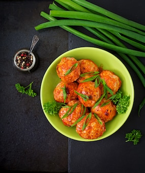 Baked meatballs of chicken fillet in tomato sauce. Free Photo