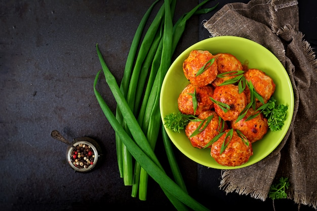 Baked meatballs of chicken fillet in tomato sauce.