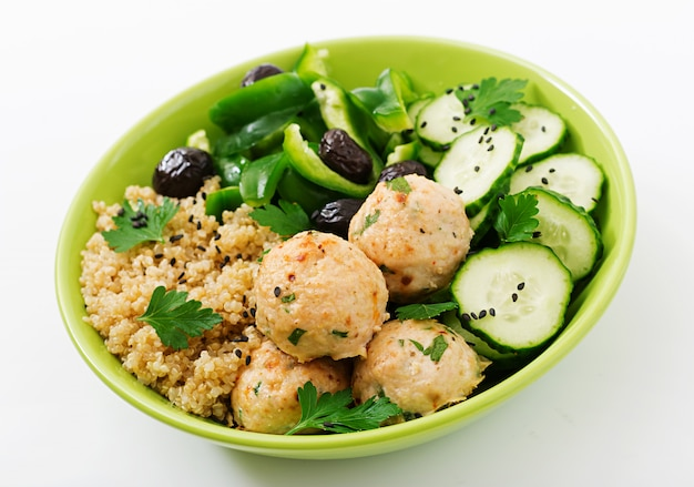 Baked meatballs from turkey fillet with garnish of quinoa and salad from fresh vegetables