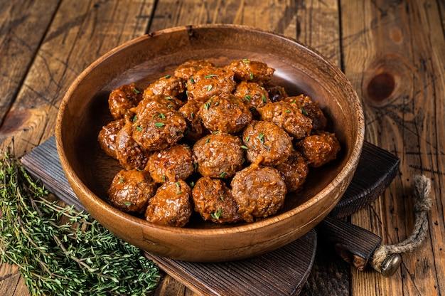 다진 쇠고기에서 토마토 소스로 구운 미트볼과 소박한 나무 접시에 백리향을 곁들인 돼지 고기