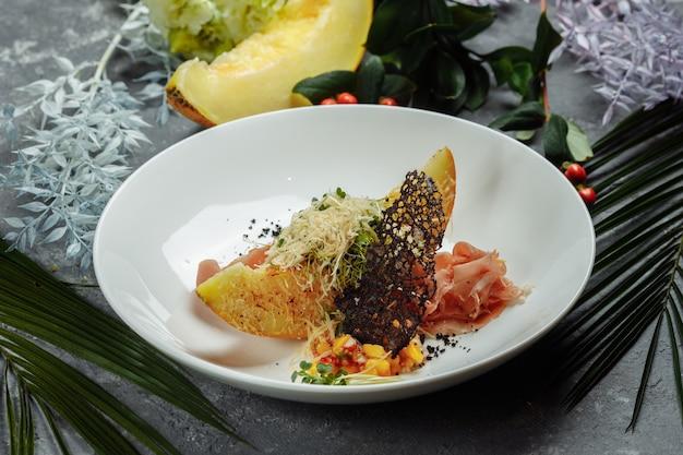 白い皿にパルメザンチーズとハモンを添えた焼きメロン。