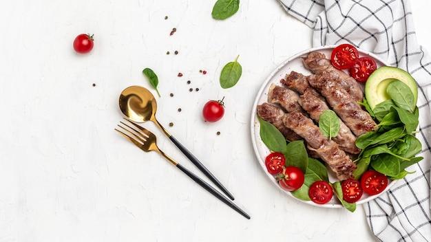 Запеченный фарш в беконе со шпинатом, авокадо и помидорами черри, полезные жиры, чистая еда для похудения. кето палеодиета. вид сверху.