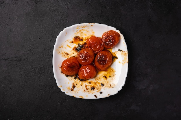 Baked minted cherry tomatoes on a white plate with traces of oil on a dark background, copy space