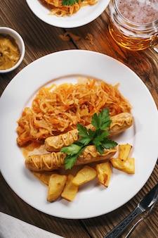 Запеченные мюнхенские сосиски с тушеной капустой и бокалом пива