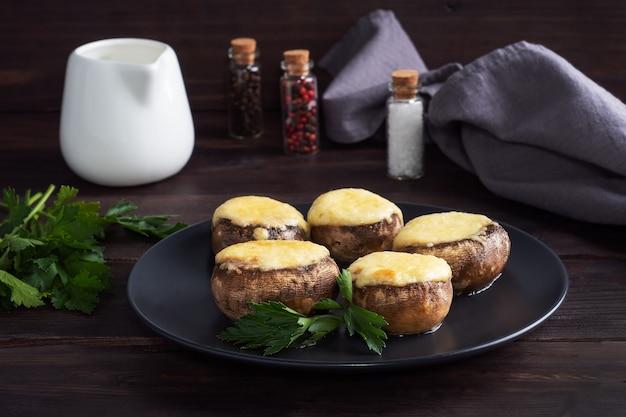 Запеченные грибы, фаршированные сыром и зеленью на черной тарелке. деревянный стол.