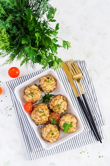 Запеченные грибы, фаршированные куриным фаршем, сыром и зеленью на легкой тарелке Premium Фотографии