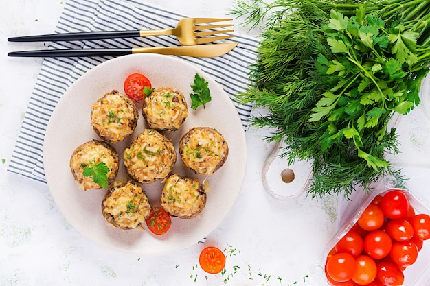 Baked mushrooms stuffed with chicken minced meat, cheese and herbs on light plate