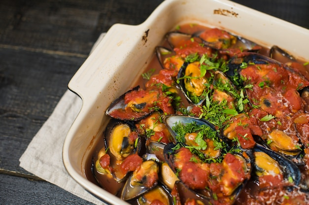 Baked mussels in tomato sauce with cilantro and parmesan.