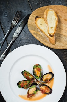 Baked mussels in tomato sauce with coriander and parmesan on a white plate.