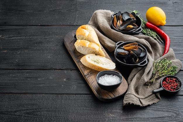 黒い木製のテーブルの背景に材料と焼きムール貝