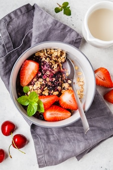 Baked oatmeal with berries and milk in a gray bowl, top view. vegan breakfast.