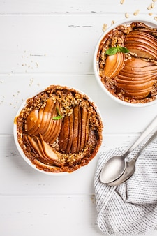 Baked oatmeal with pear and cinnamon on a white background, top view.