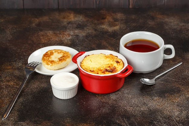 Baked omelet with golden crust in bowl with tea