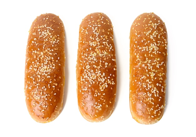 Baked oval hot dog bun, baked goods sprinkled with sesame seeds and isolated on white surface, top view