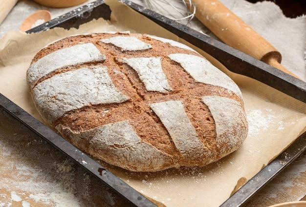 Запеченный овальный хлеб из ржаной муки на металлическом противне на столе, вид сверху