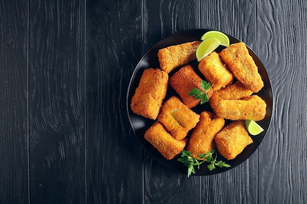 Baked in oven delicious pieces of white fish breaded with coconut and bread crumbs  on black plate on black wooden table
