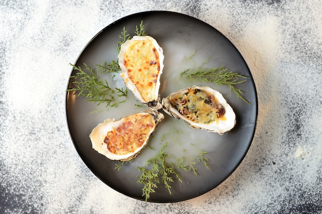 Baked oysters with cheese in a black plate