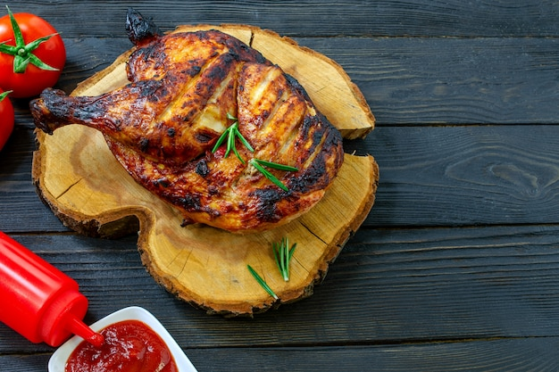 Baked part of tasty chicken, with golden brown crust, cooked on barbecue on dark wooden table.