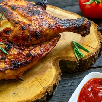 Baked part of tasty chicken, with golden crust, cooked on grill or barbecue on dark wooden table.