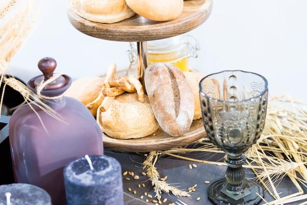 ガラスのボーカルとキャンドルの近くの木製トレイに焼きたてのペーストまたはパン、クリスマスやイースターのお祝いに誰もいないテーブルに小穂を置きます