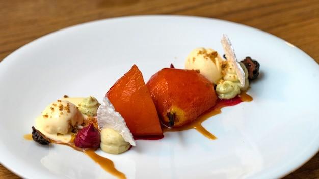 皿にバニラアイスクリームのクローズアップと焼き梨。カフェgrusha、クラスナヤポリャナ、ロシア
