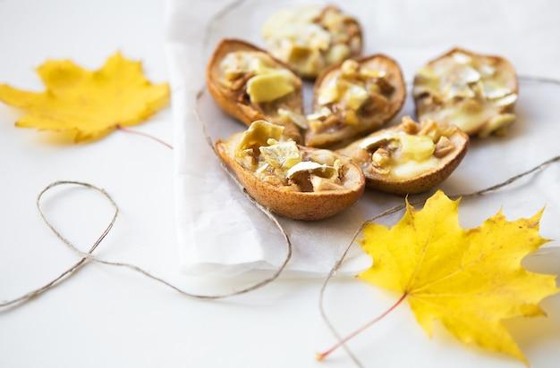 가을 노란 잎의 배경에 대해 브리 치즈와 견과류를 곁들인 구운 배, 클로즈업