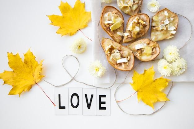 가을 노란 잎을 배경으로 브리 치즈와 견과류를 곁들인 구운 배, 사랑