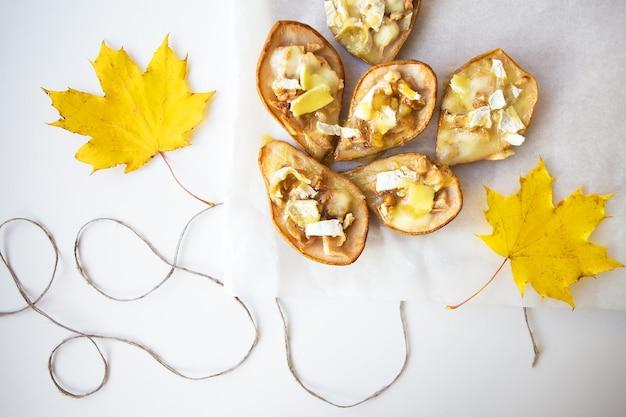 가을 노란 잎을 배경으로 브리 치즈와 견과류를 곁들인 구운 배