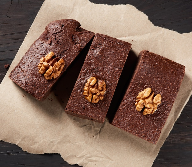 Baked pieces of brownie chocolate cake with nuts on a brown piece of paper