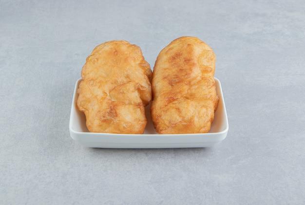 하얀 그릇에 감자와 함께 구운 피로쉬키.