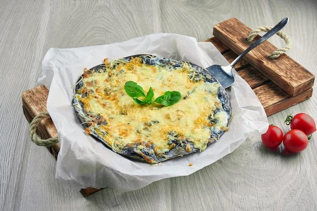 4種類のチーズ、ホワイトソース、黒の木製の表面に食材を使った組成の焼きピザ。ブラックケーキ。閉じる