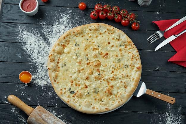 4種類のチーズ、ホワイトソース、黒の木製の表面に食材を使った組成の焼きピザ。上面図