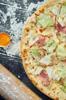 レタス、クルトン、ホワイトソース、チキンの焼きピザ。成分と組成の黒い木製のテーブルのピザシーザー。上面図