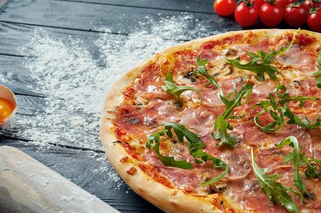 食材と組成の黒い木製のテーブルに赤いソースと溶けたチーズの生ハムで焼きたてのピザ。上面図