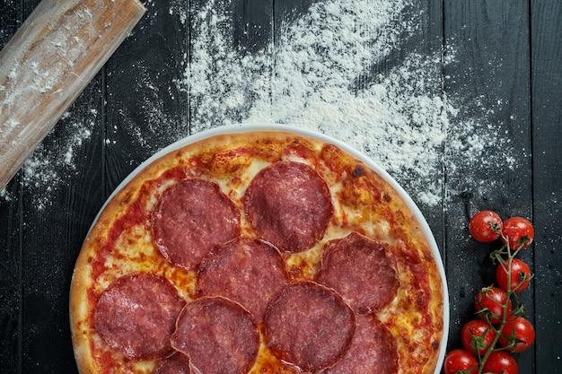 食材を使った組成のサラミチョリソとレッドソースと溶けたチーズを黒い木製の表面に焼きたてのピザ。上面図