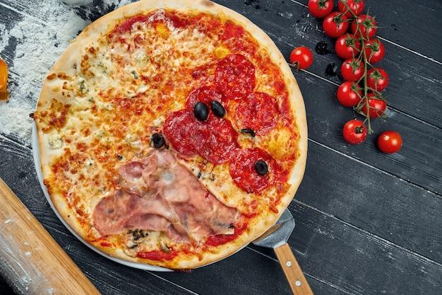 サラミ、生ハム、鶏肉のレッドソースと溶かしたチーズの食材と組成の黒い木製のテーブルで焼きたてのピザ。上面図
